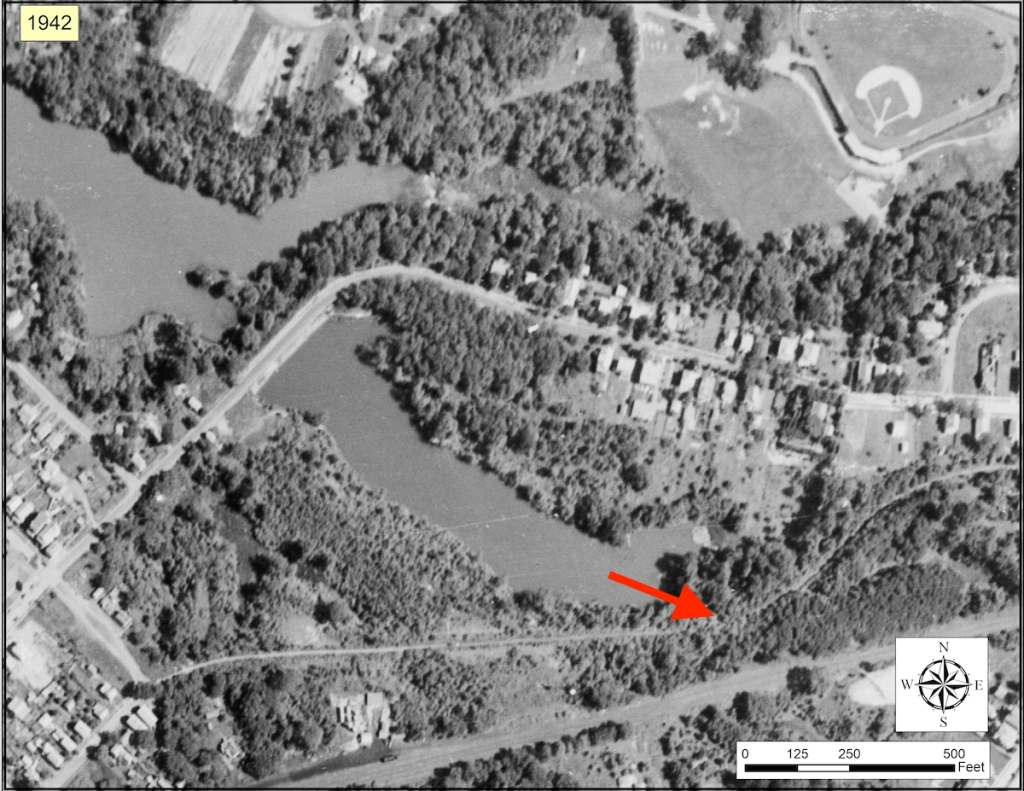 black and white aerial view of oakdale lake with red arrow pointed to old railroad