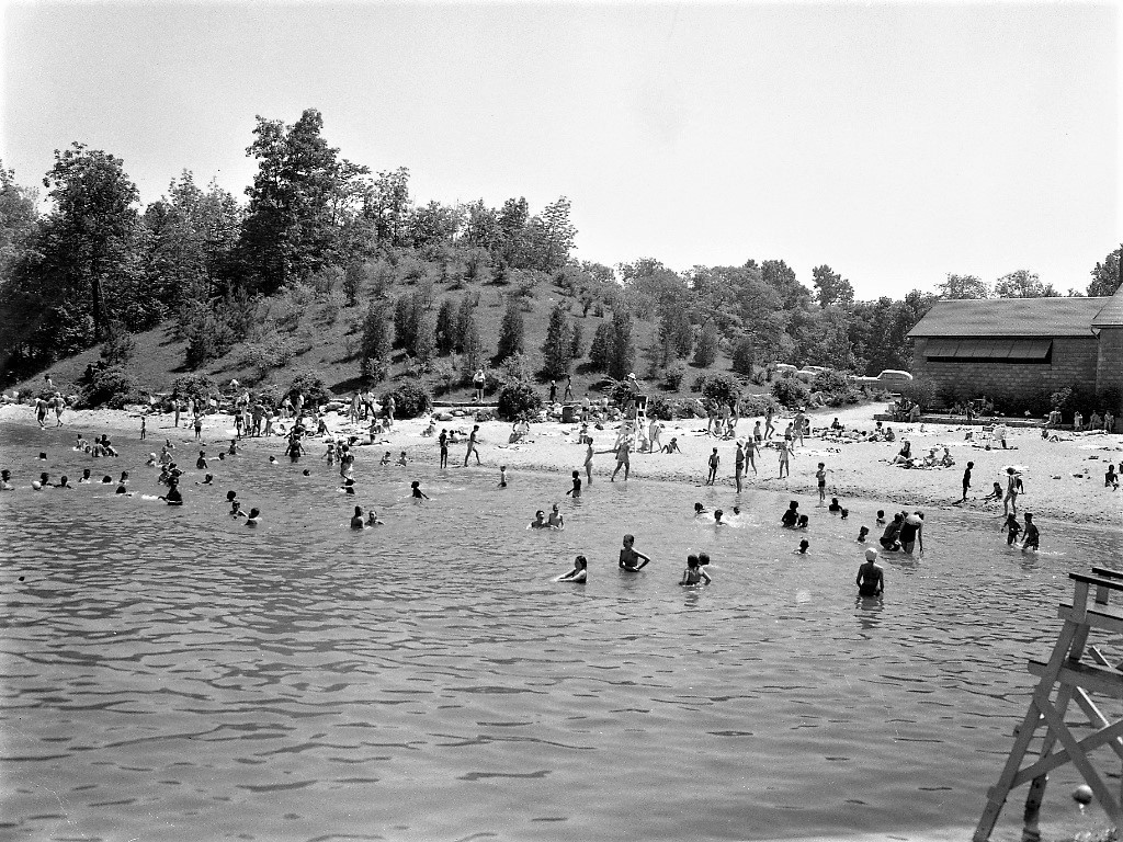 black and white photo of beach house and  lake filled with swimmers