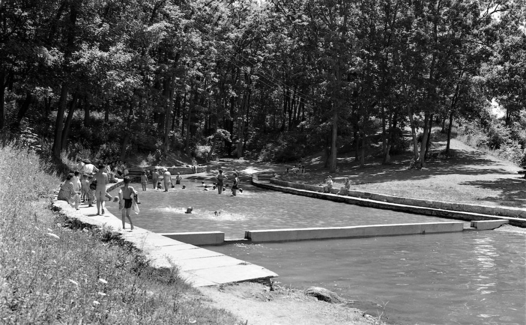 black and white image of lagoon pool full of swimmers